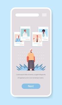 Mix lekarzy wyścigowych konsultujących się ze starszym pacjentem płci męskiej w mobilnej aplikacji do czatowania konsultacje online opieka zdrowotna medycyna porady medyczne koncepcja ekran smartfona