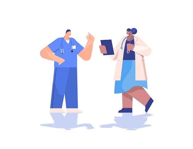 Mix lekarzy wyścigowych para w mundurach omawiająca podczas spotkania medycyna koncepcja opieki zdrowotnej pozioma pełna długość