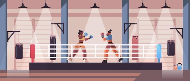 Mix race żeńskie bokserki walczące na ringu bokserskim koncepcja szkolenia niebezpiecznego zawodów sportowych nowoczesne wnętrze klubu walki