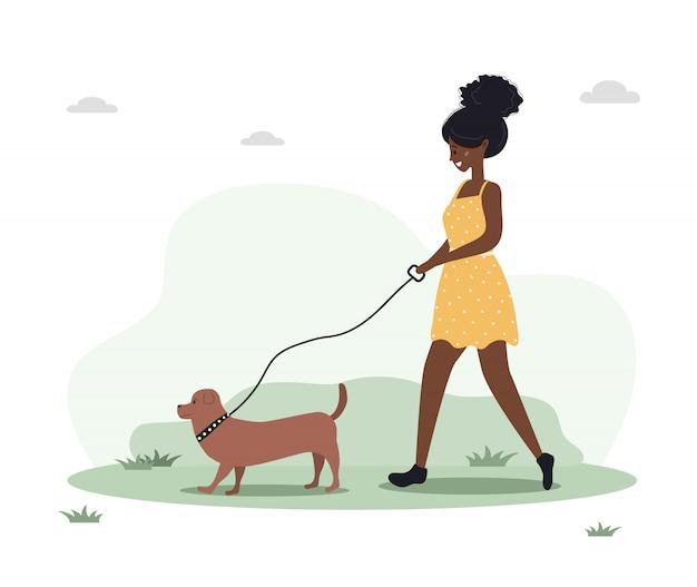 Młoda afrykańska kobieta spacery z psem po lesie. koncepcja szczęśliwa dziewczyna w żółtej sukience z jamnikiem lub pudlem. ilustracja wektorowa w stylu płaski.