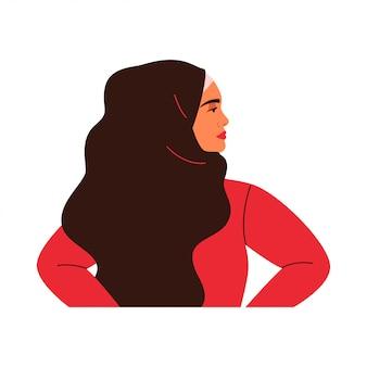 Młoda arabka stoi w profilu. muzułmańska dziewczyna ma na sobie czarny hidżab.