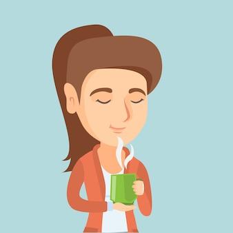 Młoda caucasian kobieta cieszy się filiżankę kawy.