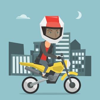Młoda caucasian kobieta jedzie motocykl przy nocą
