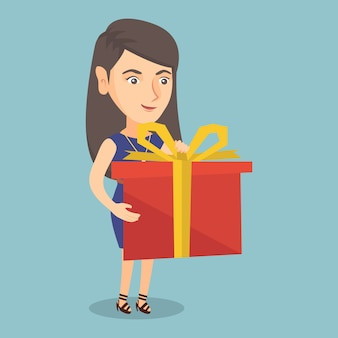 Młoda caucasian kobieta trzyma pudełko z prezentem.
