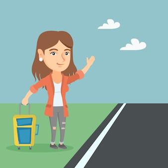 Młoda caucasian kobieta z walizką autostopem.