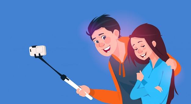 Młoda chłopiec i dziewczyna opowiada selfie fotografię na komórka mądrze telefonie z kijem