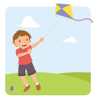 Młoda chłopiec lata latawkę w polu z czerwoną koszula