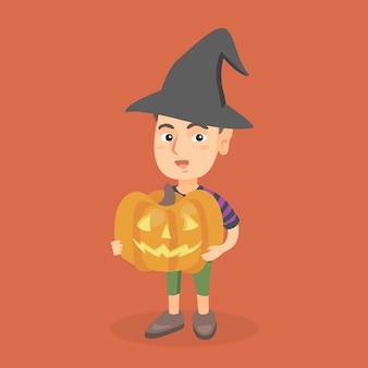 Młoda chłopiec trzyma rzeźbiącej bani na halloween.