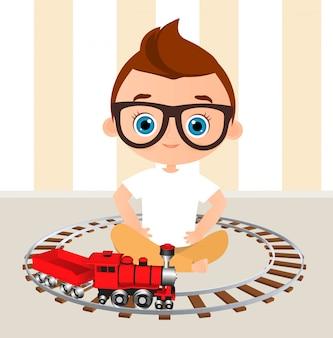 Młoda chłopiec z szkłami i zabawka pociągiem. chłopiec bawić się z pociągiem.