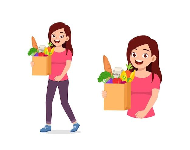 Młoda dobrze wyglądająca kobieta niesie torbę pełną zakupów spożywczych