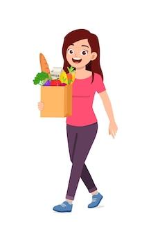 Młoda, dobrze wyglądająca kobieta nosi torbę pełną artykułów spożywczych