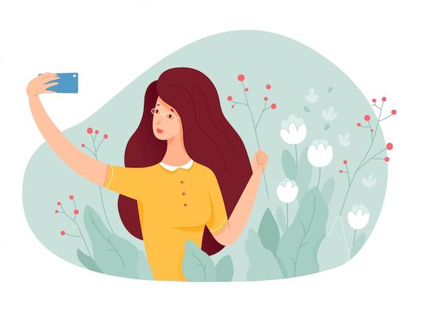 Młoda dziewczyna co selfie w ogrodzie z roślinami kwiatowymi