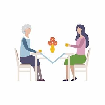 Młoda dziewczyna i jej starsza matka, babcia siedzą przy kuchennym stole i piją...
