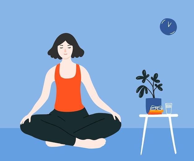 Młoda dziewczyna medytująca w pozycji ze skrzyżowanymi nogami na podłodze w niebieskim pokoju praktyka uważności w domu
