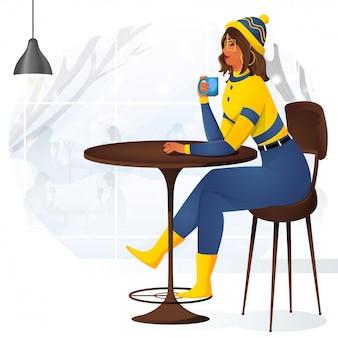 Młoda dziewczyna picia herbaty lub kawy, siedząc na krześle w sezonie zimowym.