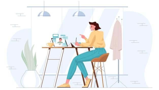 Młoda dziewczyna siedzi przy stole z tabletem podczas spotkania wideo