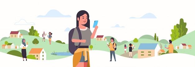 Młoda dziewczyna za pomocą smartfona komunikacja sieci społecznościowej mix wyścig ludzi rozmawiać online mobilne wiadomości aplikacji krajobraz wsi