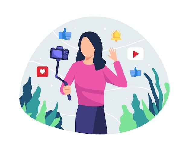 Młoda kobieta blogger lub vlongger patrząc na kamery i rozmawiając na kręcenie wideo w stylu płaski