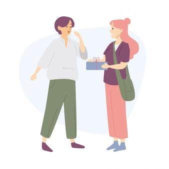 Młoda kobieta daje przyjacielowi teraźniejszości pudełku