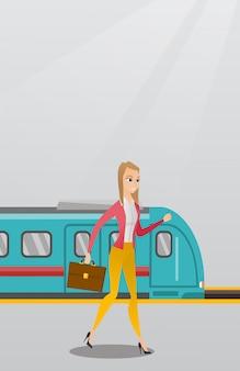 Młoda kobieta idzie na peronie kolejowym.