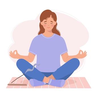 Młoda kobieta medytuje siedząc na macie do jogi