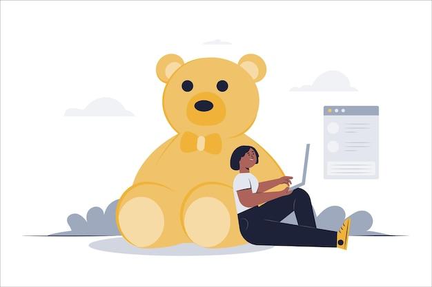 Młoda kobieta opiera się o swojego ulubionego misia i pracuje na laptopie