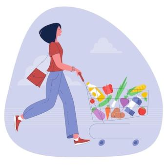 Młoda kobieta pchanie wózka supermarketu pełnego koszyka spożywczego
