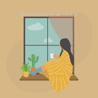 Młoda kobieta pije herbatę lub kawę i patrząc przez okno, siedząc na parapecie w domu z przytulnym kocem