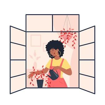 Młoda kobieta podlewa rośliny w otwartym oknie