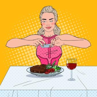 Młoda kobieta robienia zdjęć jedzenia w restauracji