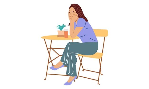 Młoda kobieta siedzi na drewnianym krześle relaksując sok do picia