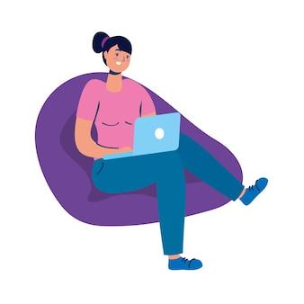 Młoda kobieta siedzi na kanapie przy użyciu charakteru technologii laptopa.