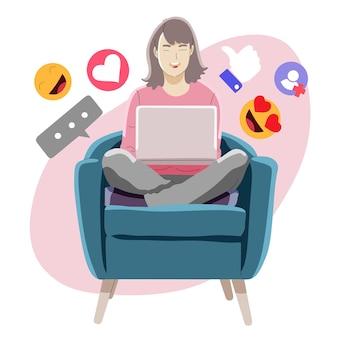 Młoda kobieta siedzi na krześle przy użyciu swojego laptopa do mediów społecznościowych
