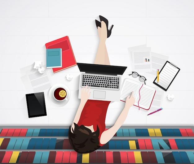 Młoda kobieta siedzi na podłodze w bibliotece