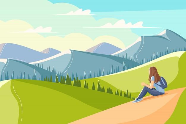 Młoda kobieta siedzi na trawie i patrzy na góry