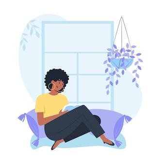 Młoda kobieta siedzi przy oknie i czyta książkę, relaksując się w domu
