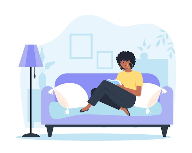 Młoda kobieta siedzi w domu na kanapie i czyta książkę