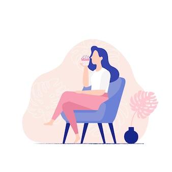 Młoda kobieta siedzi w fotelu i jeść słodka babeczka. kobieta jedzenie muffin, widok z boku