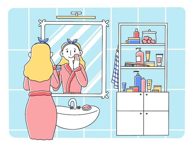 Młoda kobieta stoi przed lustrem