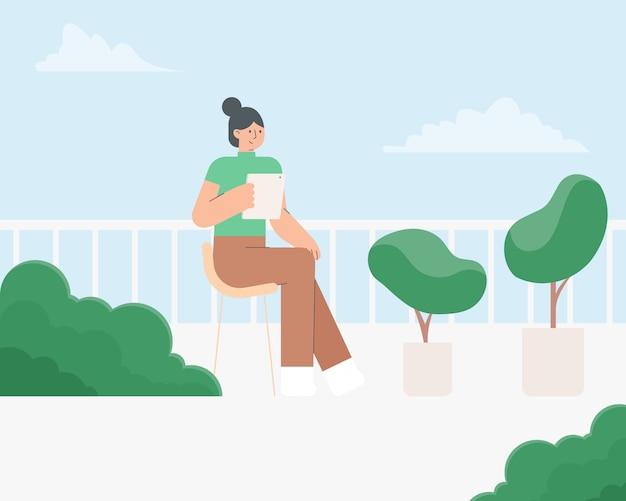 Młoda kobieta używa pastylkę przy balkonem. kobiety obsiadanie na krześle z pastylką i drzewem. koncepcja pobytu w domu. samo kwarantanna podczas wybuchu koronawirusa. ilustracja.