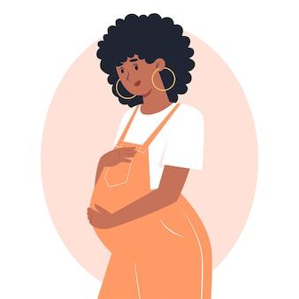 Młoda kobieta w ciąży w kombinezonie przytula brzuch rękami, ciążą i macierzyństwem