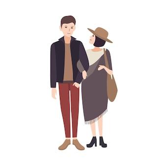 Młoda kobieta w modnym ponczo i kapeluszu stoi obok uśmiechniętego mężczyzny, trzymając go za ramię i ciepło patrząc na niego. elegancka para nastolatków. para postaci z kreskówek. ilustracja wektorowa.