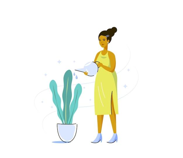 Młoda kobieta w żółtej sukience podlewania pokoju roślinnego