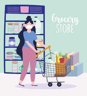 Młoda kobieta z maską i wózek na zakupy z jedzeniem w sklepie spożywczym z pudełkami ilustracyjnymi