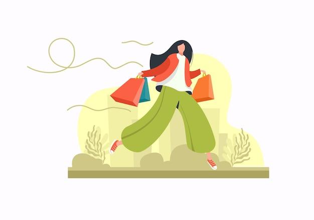 Młoda kobieta z torbami na zakupy w ręku skacze na płasko