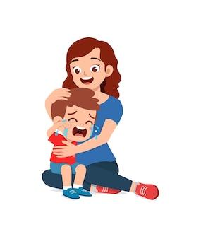 Młoda matka przytula płaczącego małego chłopca i próbuje go pocieszyć