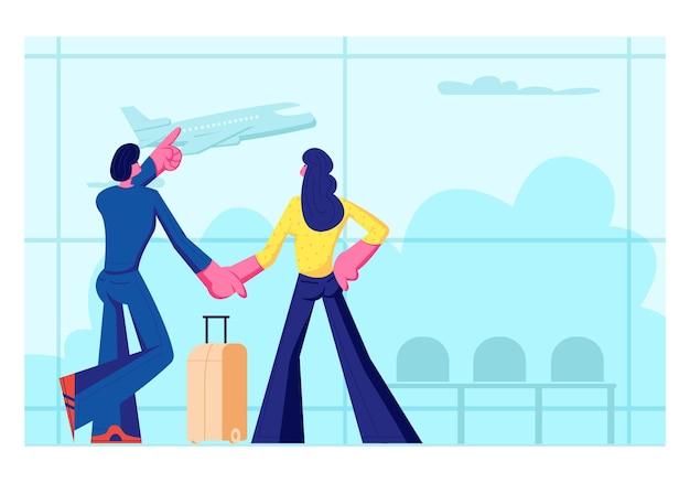 Młoda para kochających się na wypoczynek. mężczyzna i kobieta stoją w terminalu lotniska, czekając na lot, oglądając lecący samolot przez okno. letnie wakacje, miesiąc miodowy. ilustracja wektorowa płaski kreskówka