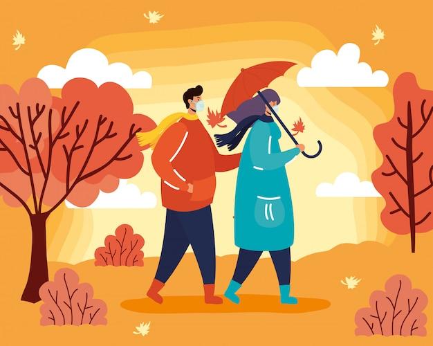 Młoda para ubrana w maski medyczne w scenie sezonu jesiennego