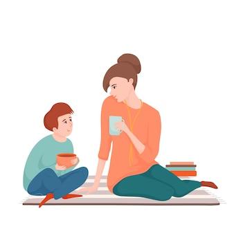 Młoda piękna matka i nastoletni syn siedzi na dywanie, pije herbatę i rozmawia, spędza razem czas