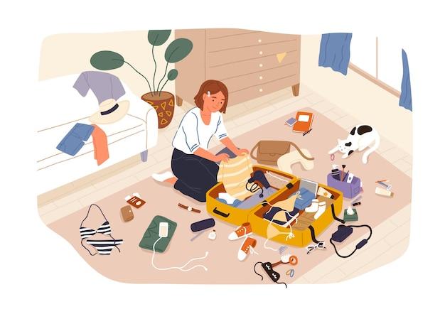 Młoda śliczna uśmiechnięta dziewczyna siedzi na podłodze i pakuje jej walizkę lub torbę i przygotowuje się do podróży lub podróży